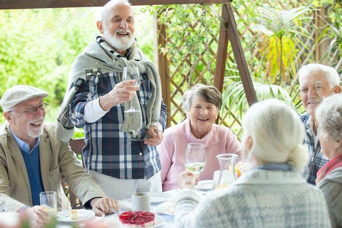 Glückliche Gruppe von pensionierten Freunden Spaß während der Geburtstagsfeier im Garten