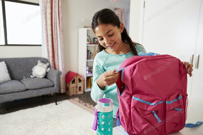 Young Girl In Bedroom Zipping Up Bag Ready For School
