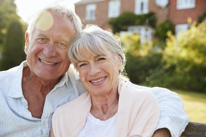 Senior Couple Sitting On Garden Bench In Evening Sunlight
