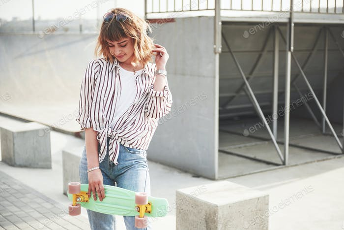Stylish beautiful young woman with a skateboard, on a beautiful summer sunny day