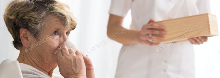 Senior Frau bläst ihre Nase