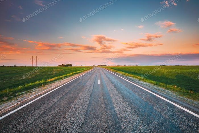 Asphalt Land Open Road Durch Frühlingsfelder Und Wiesen In Sonnigen Abend. Landschaft in der Frühe