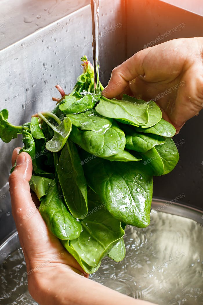 Male hands washing spinach