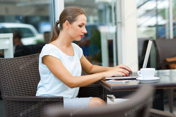 Junge Geschäftsfrau sitzt in einem Café mit einem Laptop und Kaffee