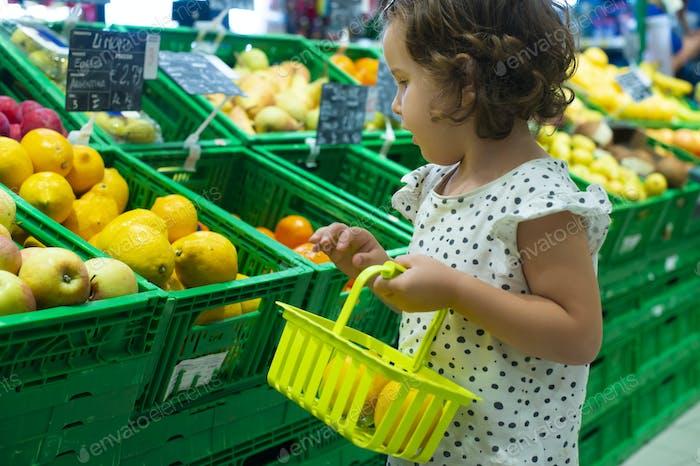 Little girl buying lemons in supermarket. Child hold small baske