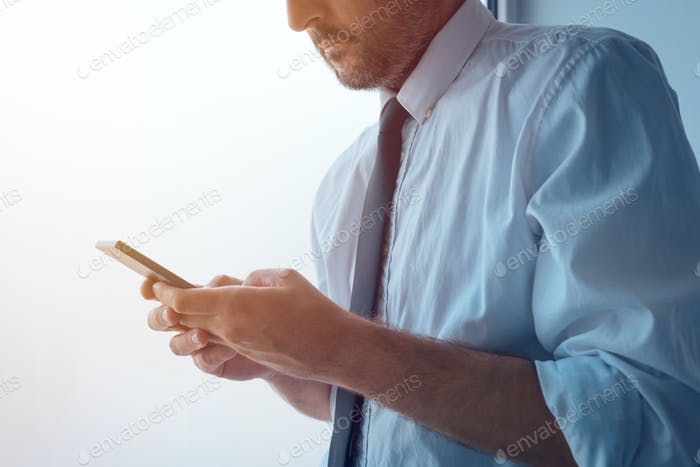 Бизнесмен, стоящий рядом с офисным окном и смс