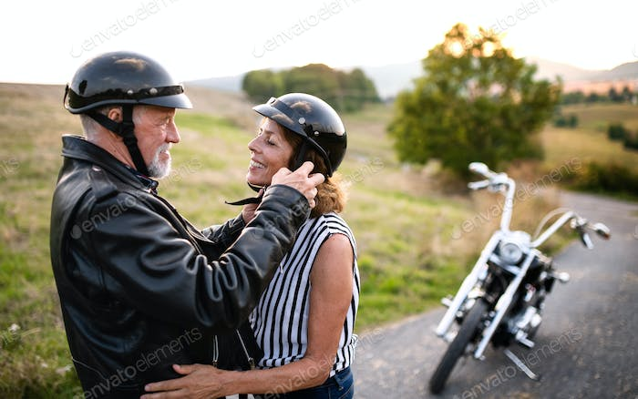 A cheerful senior couple travellers in love with motorbike in countryside.