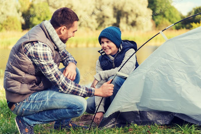 happy father and son setting up tent outdoors