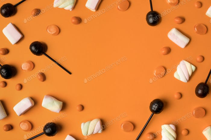 top view of sweet marshmallows and halloween candies on orange
