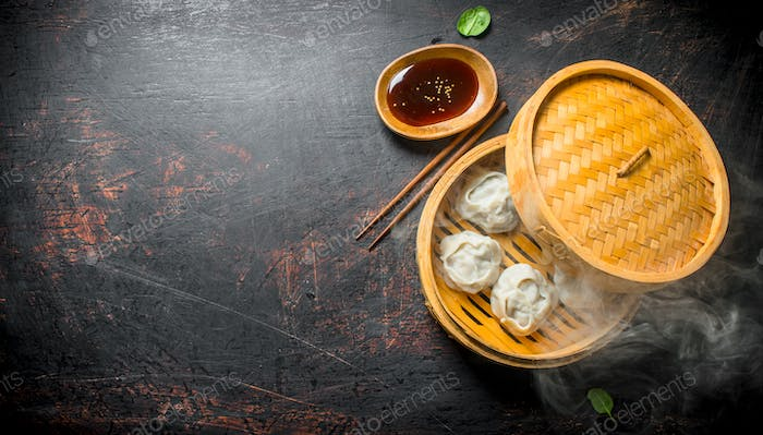 Hot aromatic manta dumplings in bamboo steamer with soy sauce.