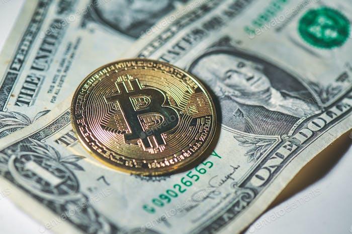 Moneda Bitcoin descansando en dólares de papel