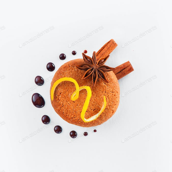 Cookie decorated with lemon zest, chocolate drops, cinnamon and anise star on a white background