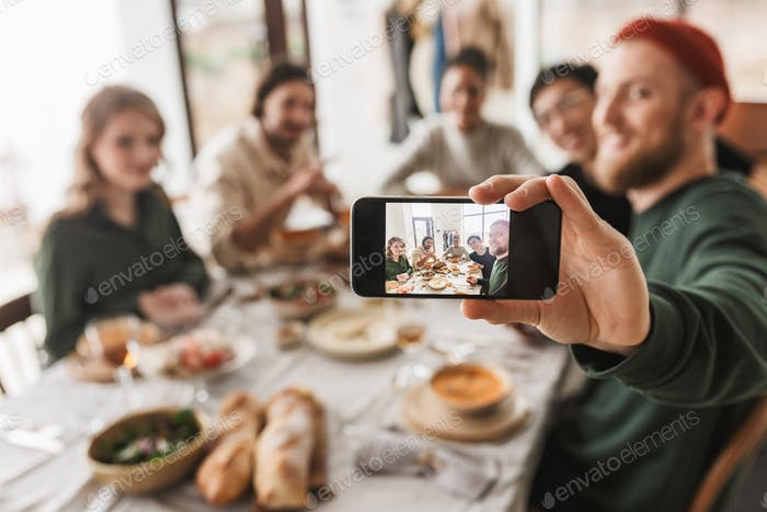 Young colleagues joyfully taking selfie on cellphone having lunch in cozy cafe