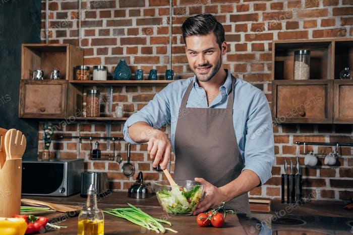 handsome man in apron making salad
