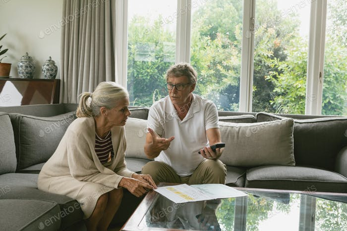 Active senior Caucasian couple calculating domestic bills on sofa in living room at comfortable home