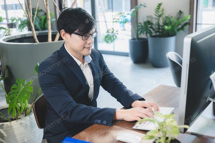 selbstbewusster professioneller Geschäftsmann, der im modernen Geschäftsbüro mit Laptop arbeitet