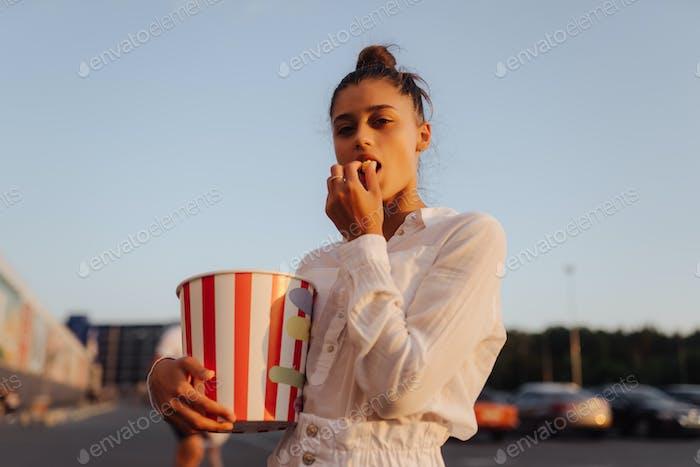 Junge süße Frau hält Popcorn auf einem Parkplatz eines Einkaufszentrums