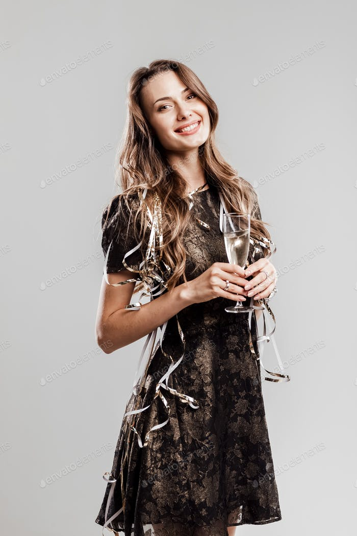 Beautiful girl dressed in stylish elegant black dress smiles and holds glasses of champagne on a