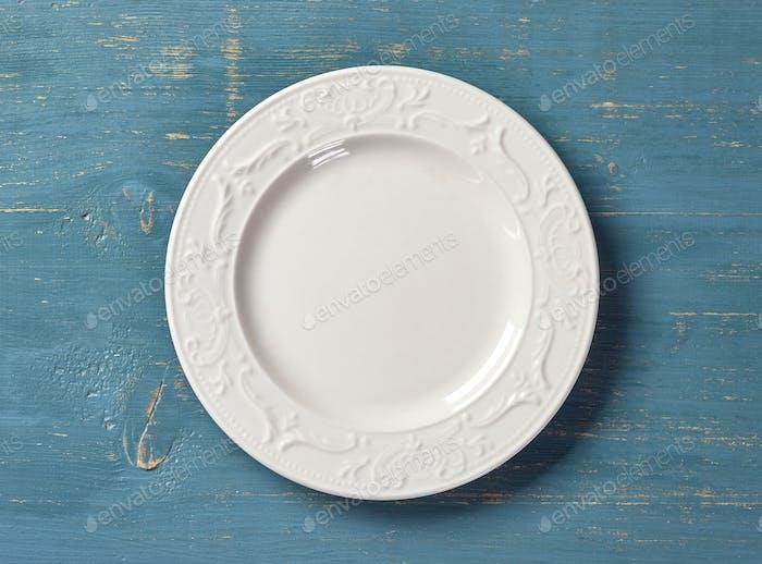 weißer Teller auf blauem Holztisch