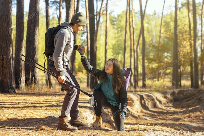 Handsome hiker helping his girlfriend uphill in the forest