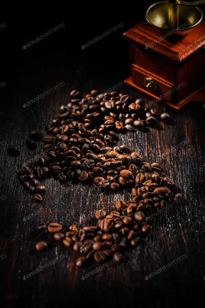 Granos de café sobre fondo oscuro con molino de café