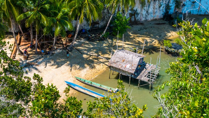 Local people tap new location, Bamboo Hut and Boats on Beach in low Tide, Kabui Bay near Waigeo
