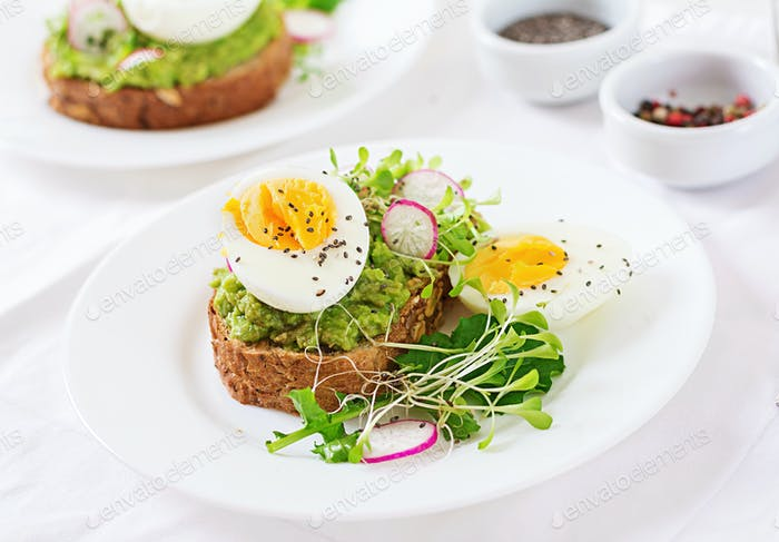 Thumbnail for Healthy food. Breakfast. Avocado egg sandwich with whole grain bread on white wooden background.