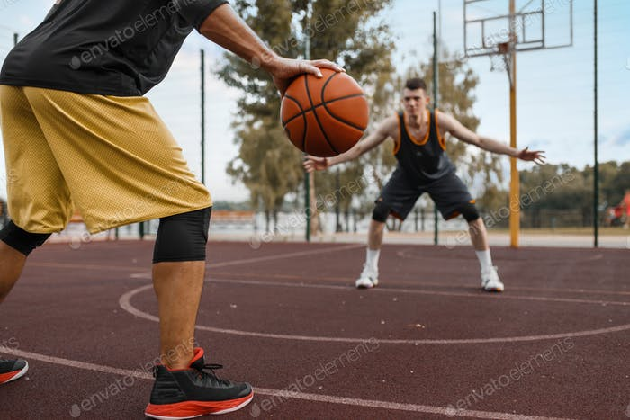 Two basketball players work out tactics outdoor