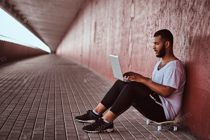 African-American bearded guy working on a laptop while sitting on a skateboard under a bridge.