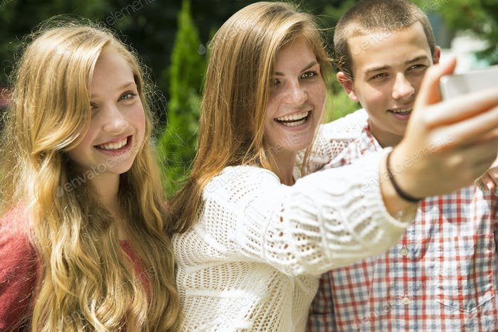 Three young people, two girls and a boy, posing and taking selfy photographs.
