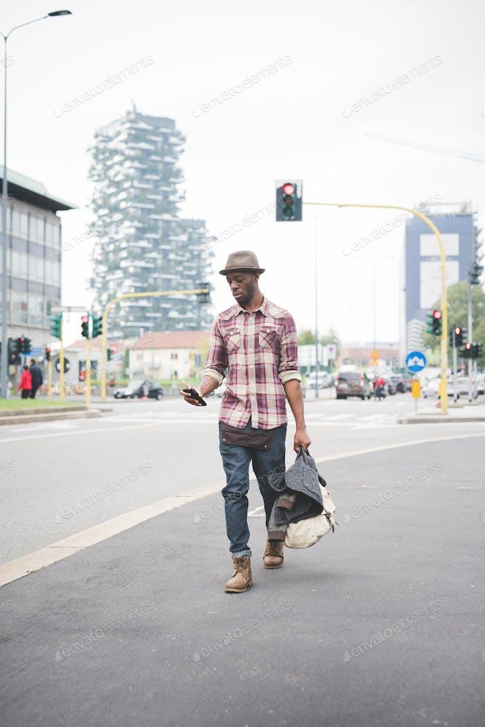 Junge gutaussehende afro schwarzen Mann zu Fuß auf der Straße der Stadt,