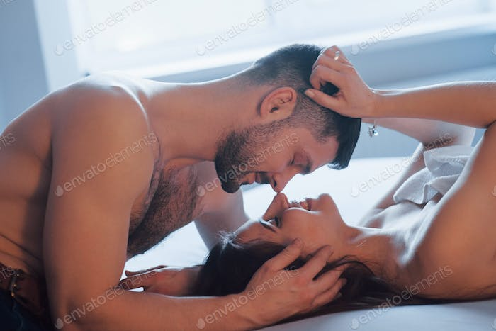 Having good time. Sexy couple lying on the bed and enjoying themselves at morning time