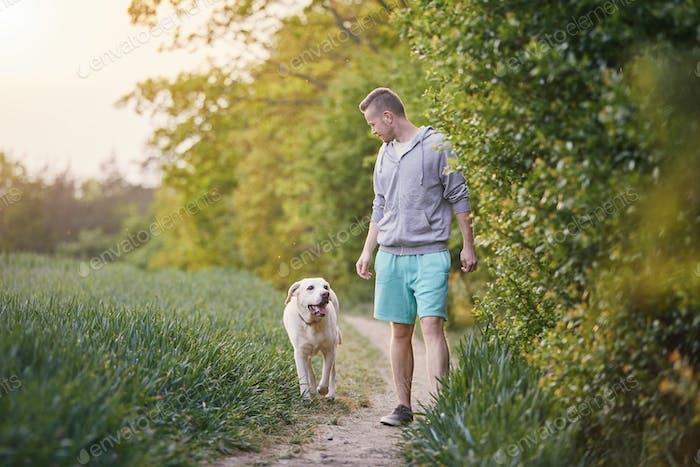 Mann mit Hund auf Gehweg
