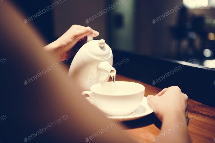 Frau gießt ein heißes Getränk
