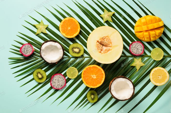 Exotic fruits and tropical palm leaves on pastel turquoise background - papaya, mango, pineapple