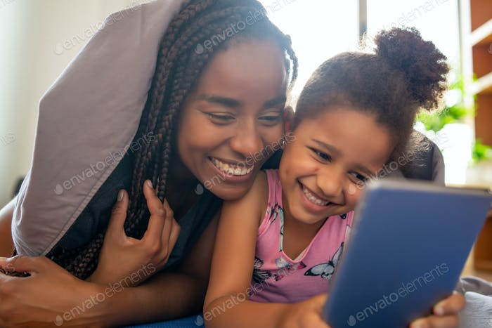 Mother and daughter using digital tablet at home.