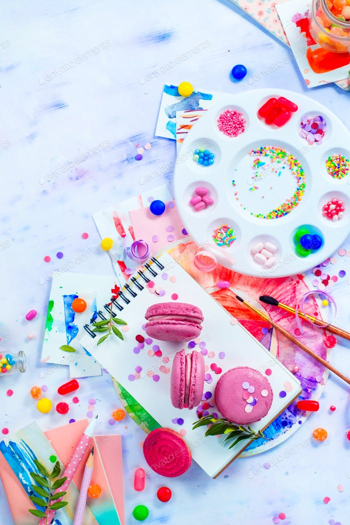 Pink macarons in a colorful party activity concept with confetti, artist tools, brushes, palette and
