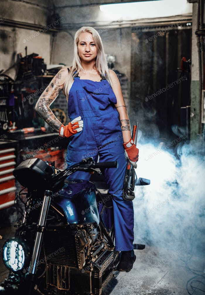 Beautiful female mechanic with tattooed hands in work overalls posing for a camera in workshop