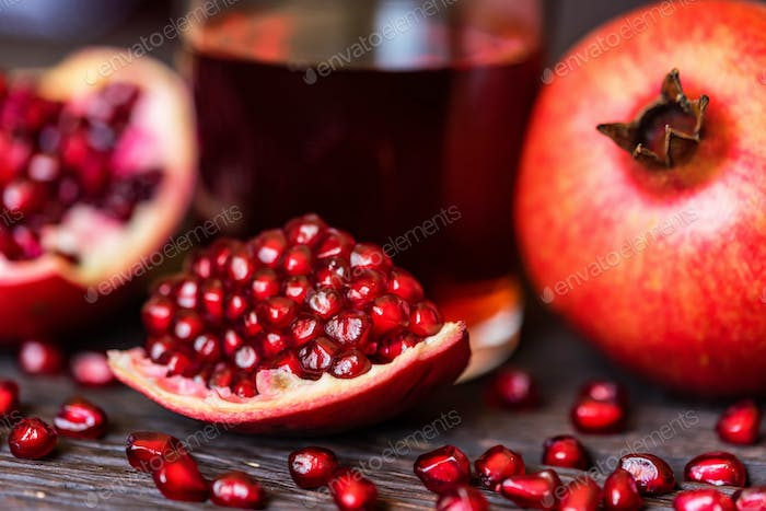 Ripe pomegranates with glass of juice on table