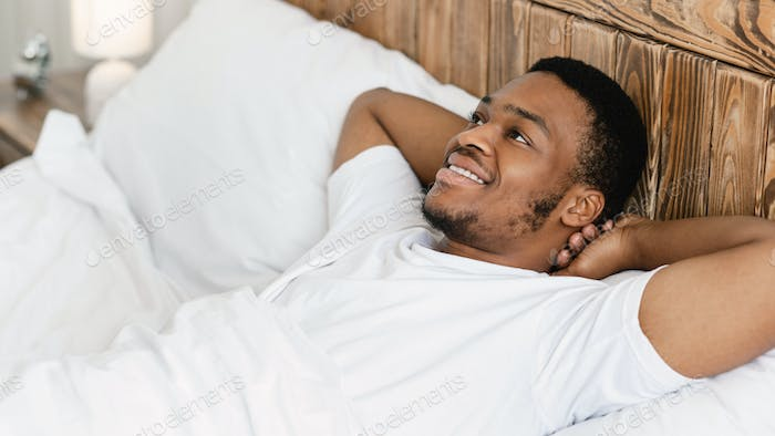 Happy African Guy Lying Awake In Bed In The Morning