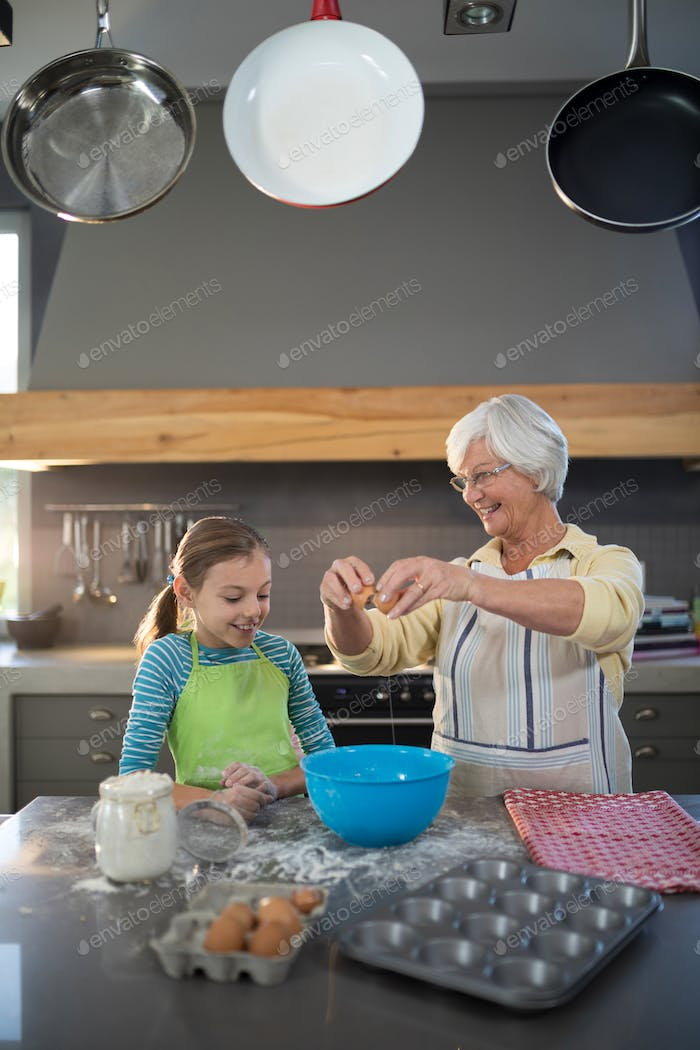 Smiling grandmother showing granddaughter to break eggs
