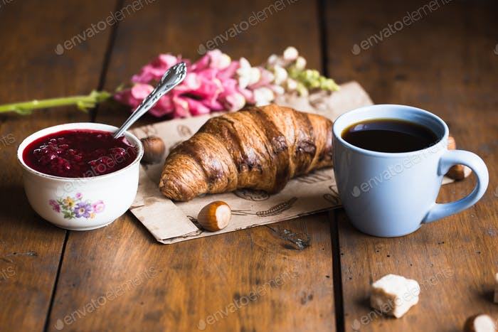 Coffee croissant on old wooden table background