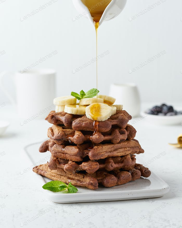 Chocolate banana waffles with maple syrup flow in milk jug, creamer on white table