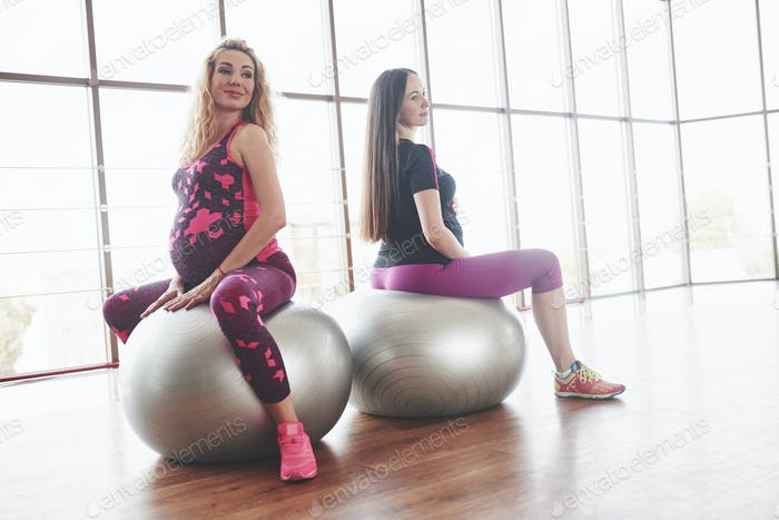 Two pregnant women sitting on stability balls in the room with wide windows