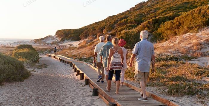 Group Of Senior Friends Walking Along Boardwalk At Beach On Summer Group Vacation