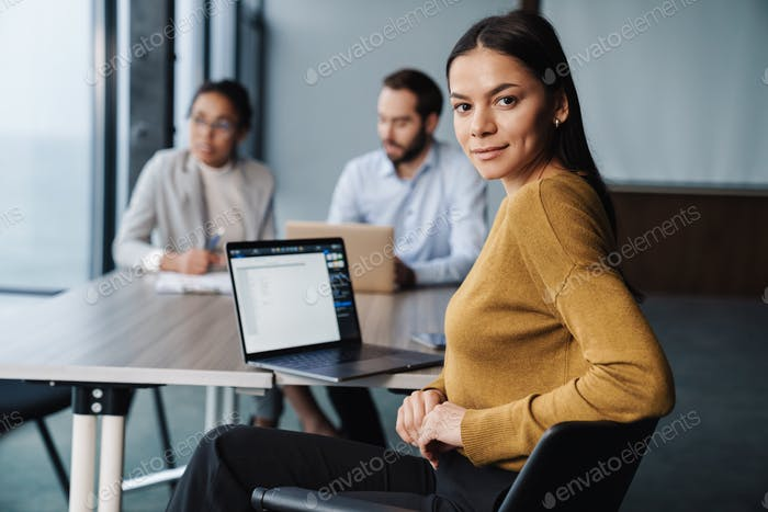 Image of young female and male colleagues working on laptops in office