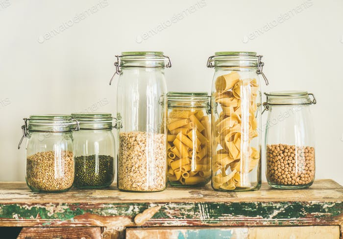 Uncooked cereals, grains, beans and pasta in jars on table