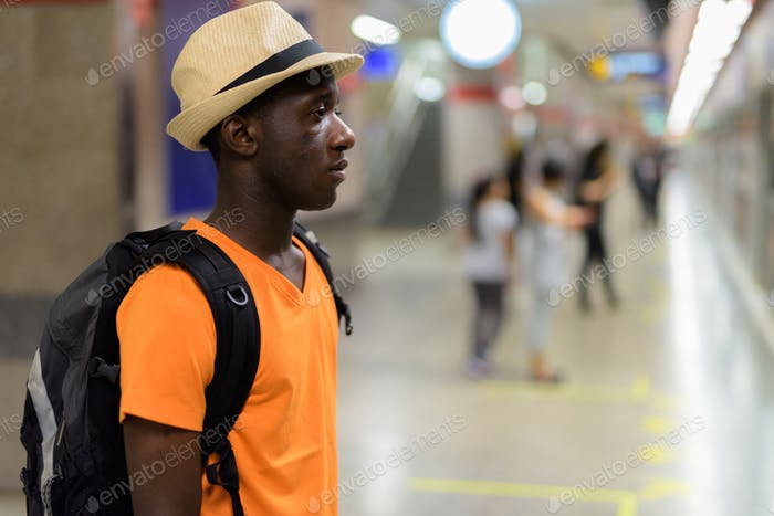 Profile view of young black African man waiting for train