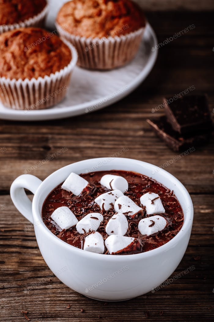 A cup of hot chocolate or cocoa with marshmallows on wooden background