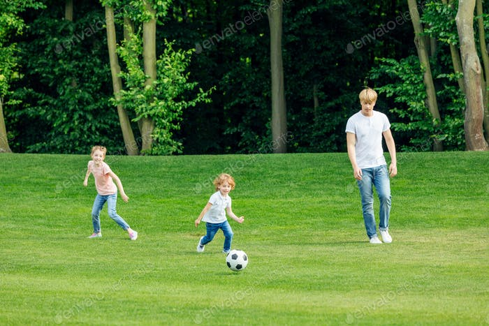 happy young father with two adorable children playing soccer on green lawn at park